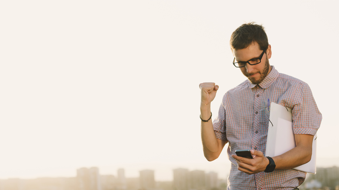 Man looking at mobile doing fist pump in air