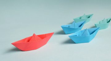 Red, blue and green paper boats