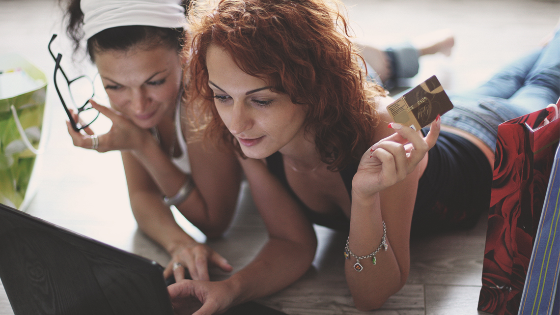 Two girls holding a credit card looking at a laptop