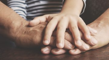 close up of child and parents hands laid on top of each other in team-like fashion