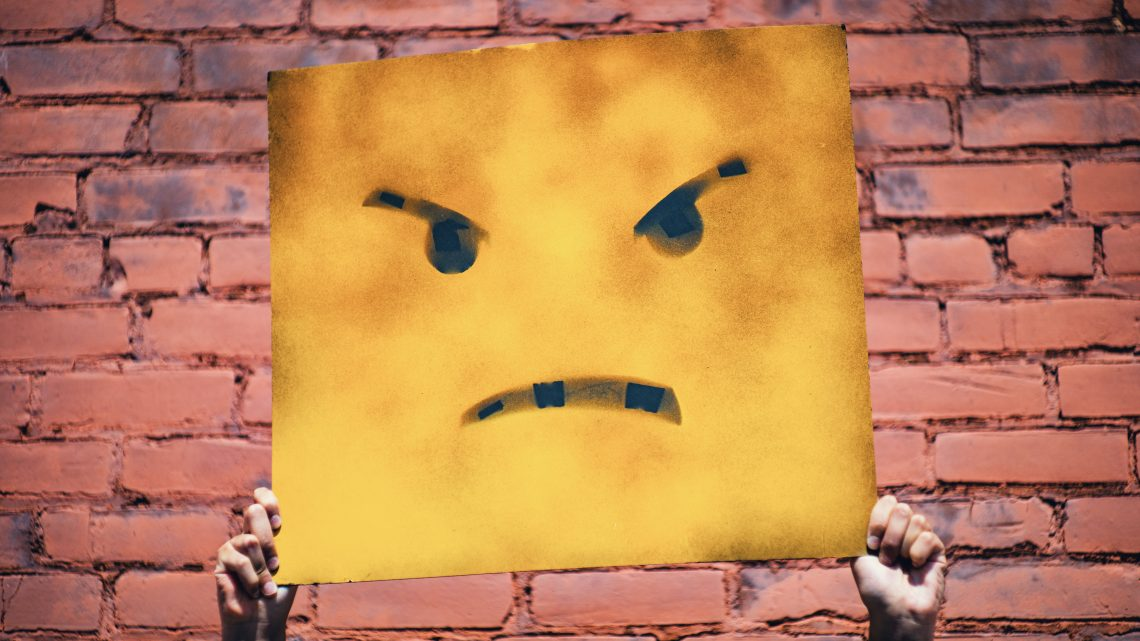 A square angry face against a brick wall
