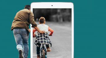 father helping son ride bike with ipad overlaid on top