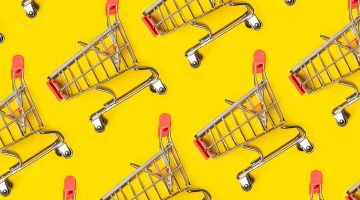 Multiple mini shopping trollies against a bright yellow background
