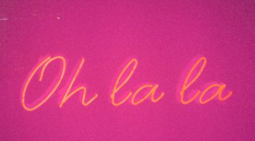A yellow neon light sign reading 'Oh la la' on a pink background
