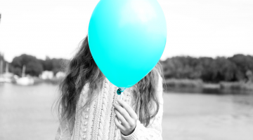 bright balloon covering a persons face