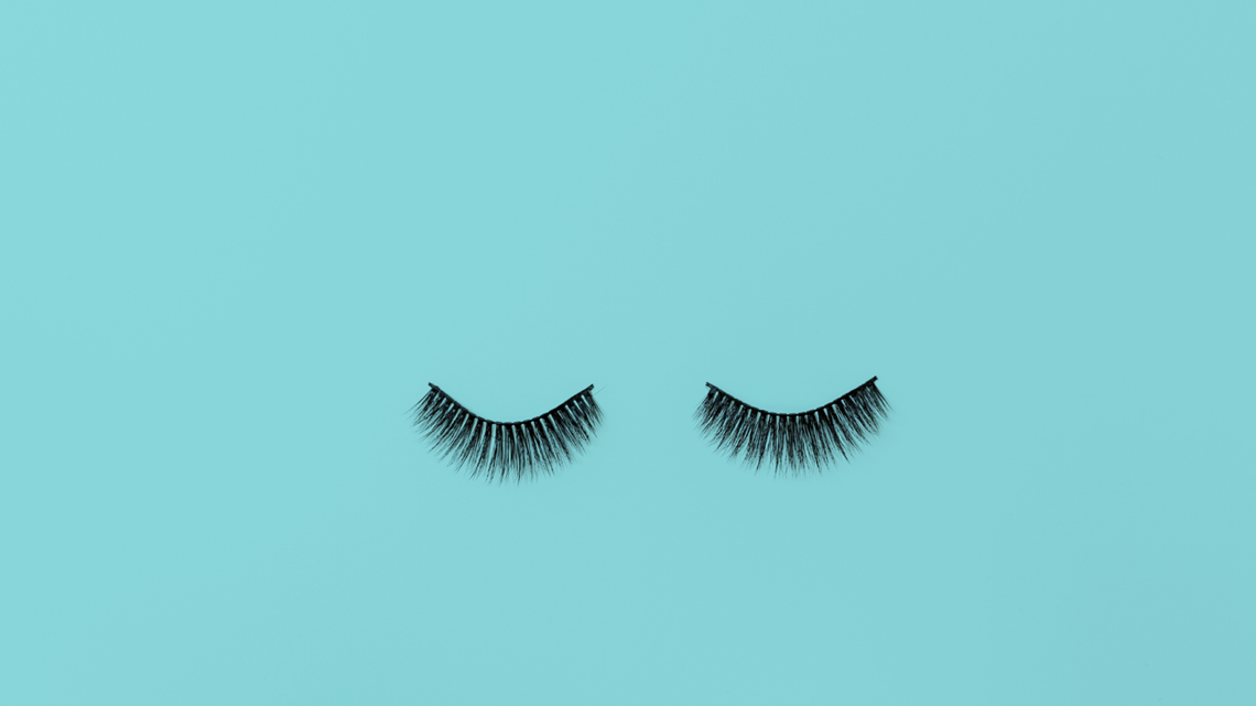 fake eyelashes on light blue background