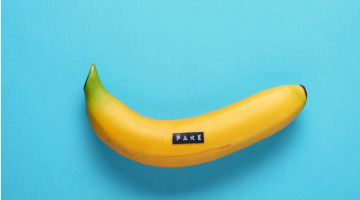 """fake banana with a label maker label that reads """"fake"""""""