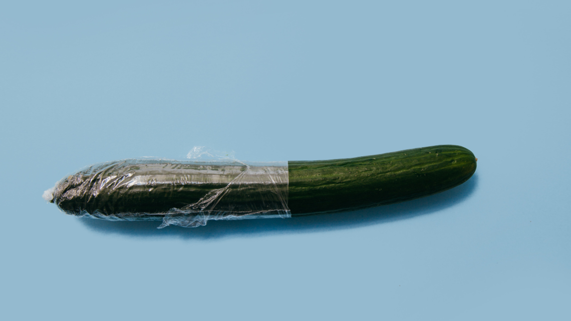 half opened saran-wrapped cucumber on light blue background