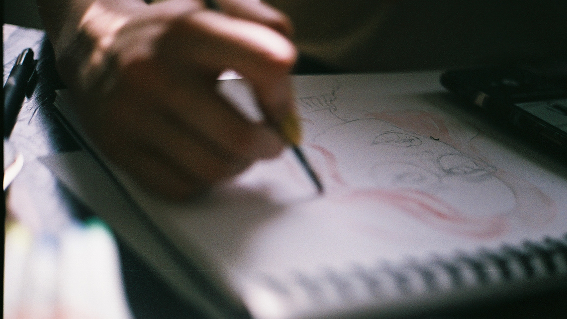 image of note pad as someone draws a face