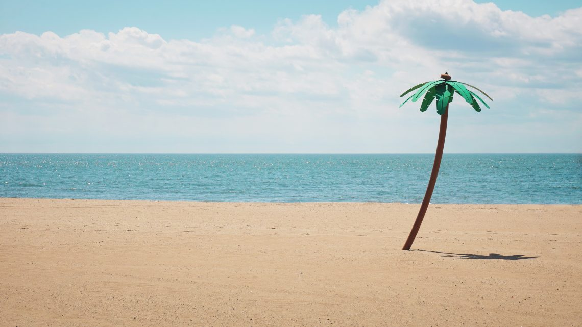 Green artifical palm tree on a beach