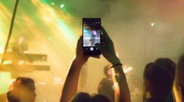 Someone holding up a phone to live stream a concert
