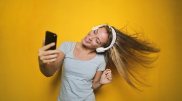 Woman listening to music while filming on-phone