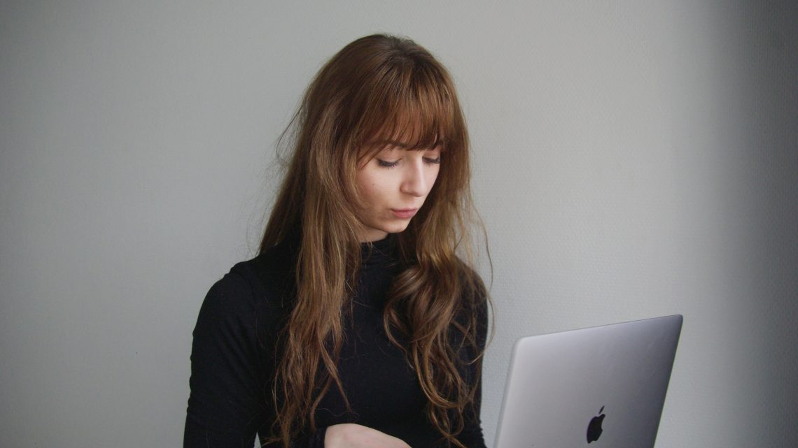 A young person looking at their laptop with a neutral look on their face