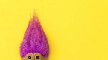 troll with pink hair on yellow background