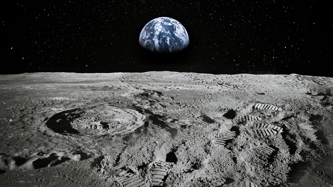 surface of moon showing footprints with view of earth in the background