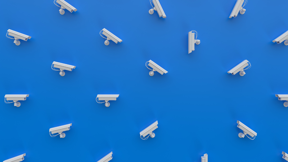 several white security cameras pointing at one area on blue background