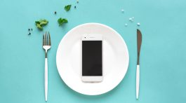 phone on a dinner plate with fork and knife on either side on teal background