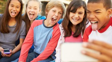Group Of Children Sitting On Bench In Mall Taking Selfie Laughing And Smiling