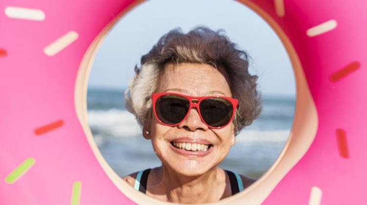 Older person wearing sunglasses smiling at a beach inside a donut image filter