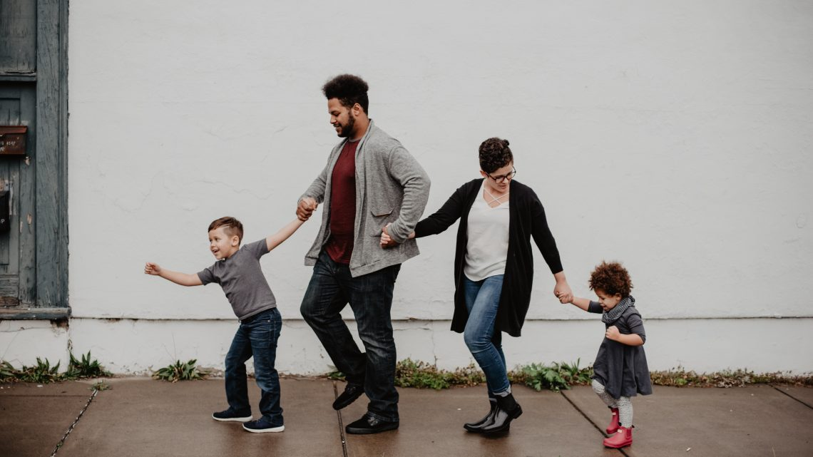 family-of-four-walking-at-the-street-2253879