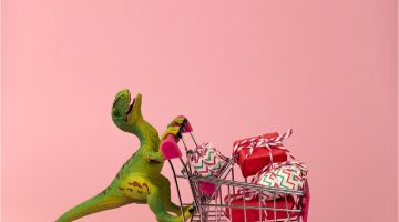 A toy dinosaur pushing a toy shopping cart filled with presents, against a pink background