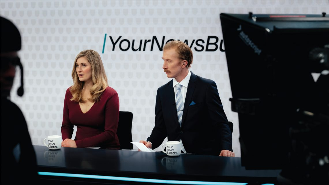 Two people sitting at an news anchor desk