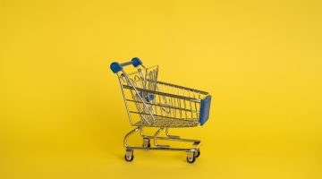 Picture of a small supermarket trolley on a yellow background