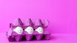 A purple egg carton with three eggs inside showing happy, angry and neutral expressions.