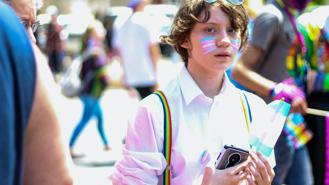 Person with facepaint at a pride event holding a device