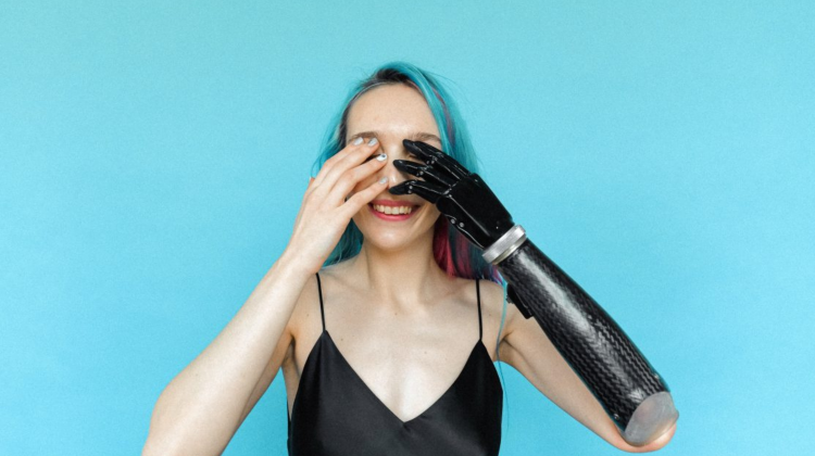 A female who has a prosthetic arm raising her hand to her head