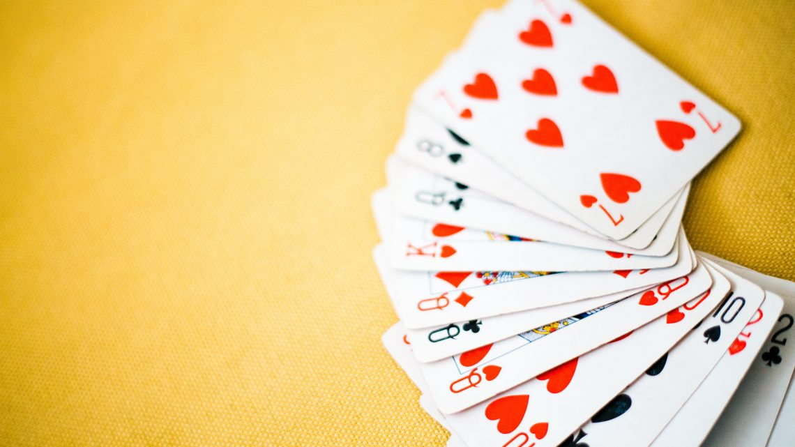 Playing cards spread out on a yellow table
